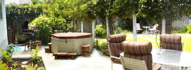 Back patio with hot tub, outdoor dining, and plants, adjacent to grassy area. - Kate's Cottage by the Sea, in Santa Cruz, CA - Santa Cruz - rentals