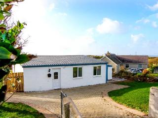 HARBOUR LIGHTS, detached, ground floor cottage, 5 mins walk from beach, woodburning stove, hot tub and sauna, in Church Bay, Ref - Amlwch vacation rentals